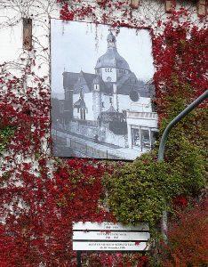Massives Gebäude ohne Fenster, bewachsen mit Efeu. An der Fassade hängt das Bild eines jüdischen Gotteshauses.