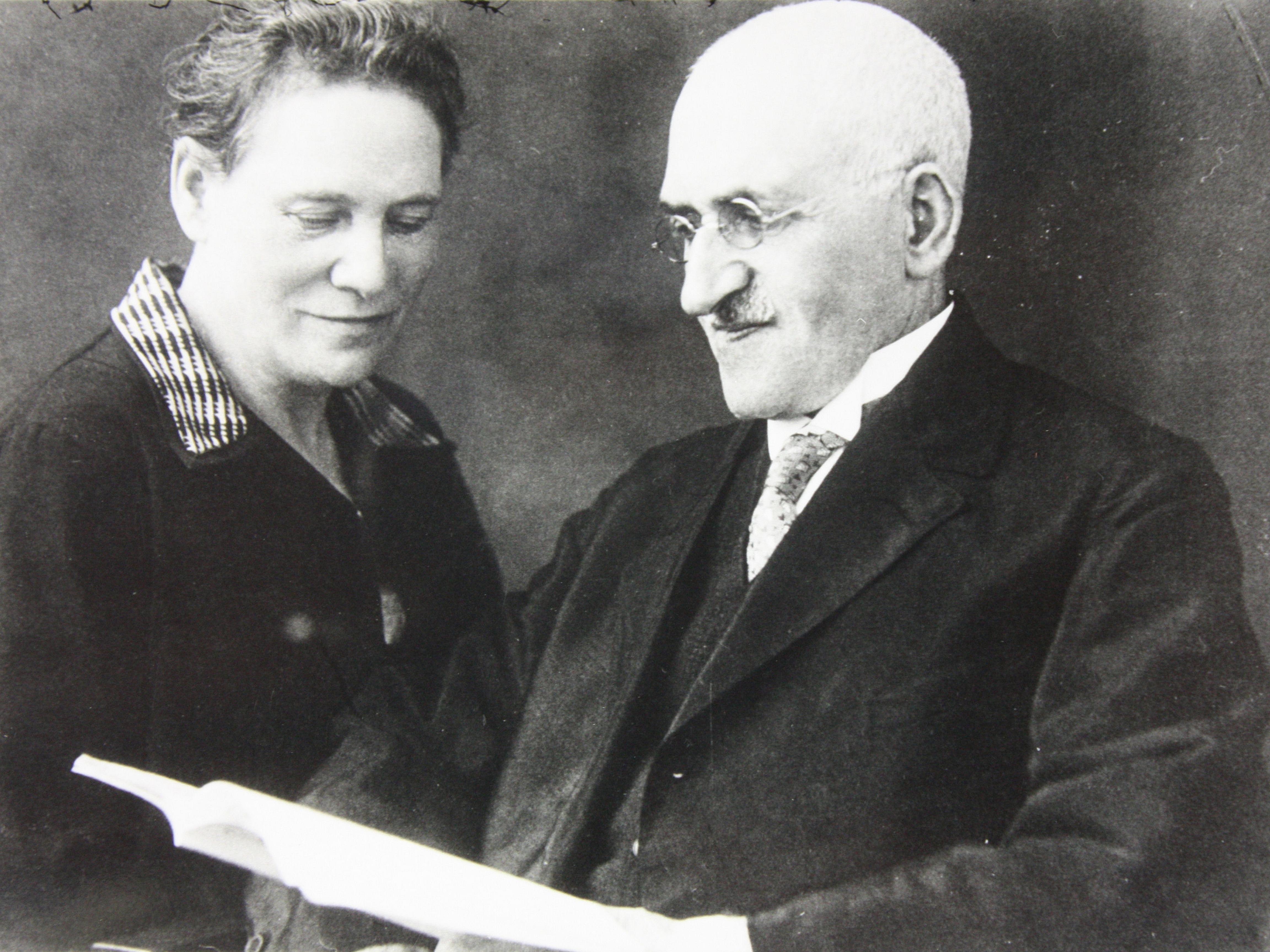 Eine Frau sitzt links. Sie schaut auf ein Buch, dass der Mann, der neben ihr sitzt in den Händen hält. Er blickt ebenfalls auf das Buch.
