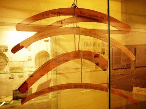 """In einer Glasvitrine hängen verschiedene, hölzerne Kleiderbügel. Eines davon trägt die Aufschrift """"Kaufhaus zur billigen Quelle L. Reches Marburger Tor 4 & 24"""""""