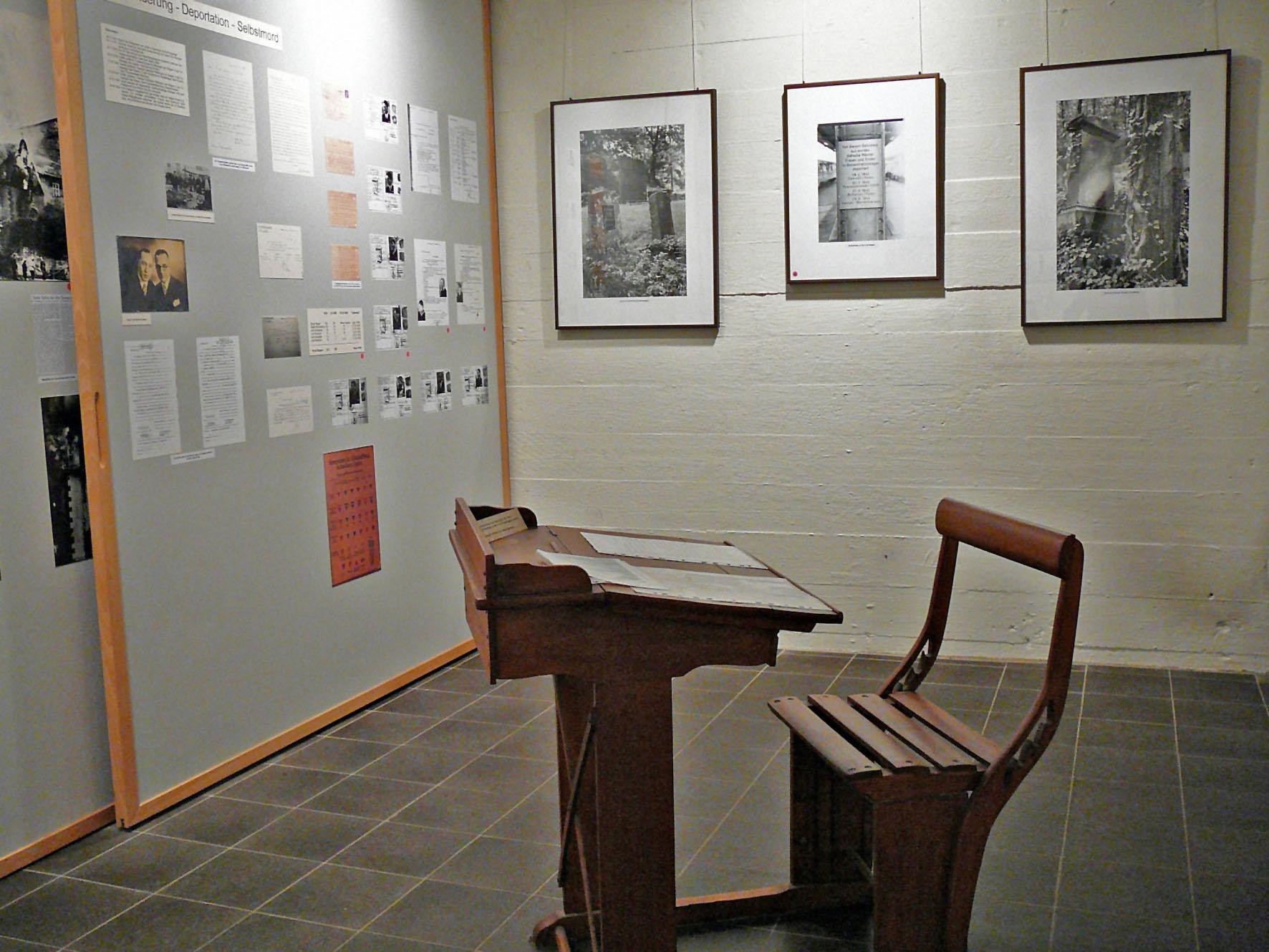 Ein altes, hölzernes Schreipult mit Sitzbank im Vordergrund, Ausstellungstafeln im Hintergrund.
