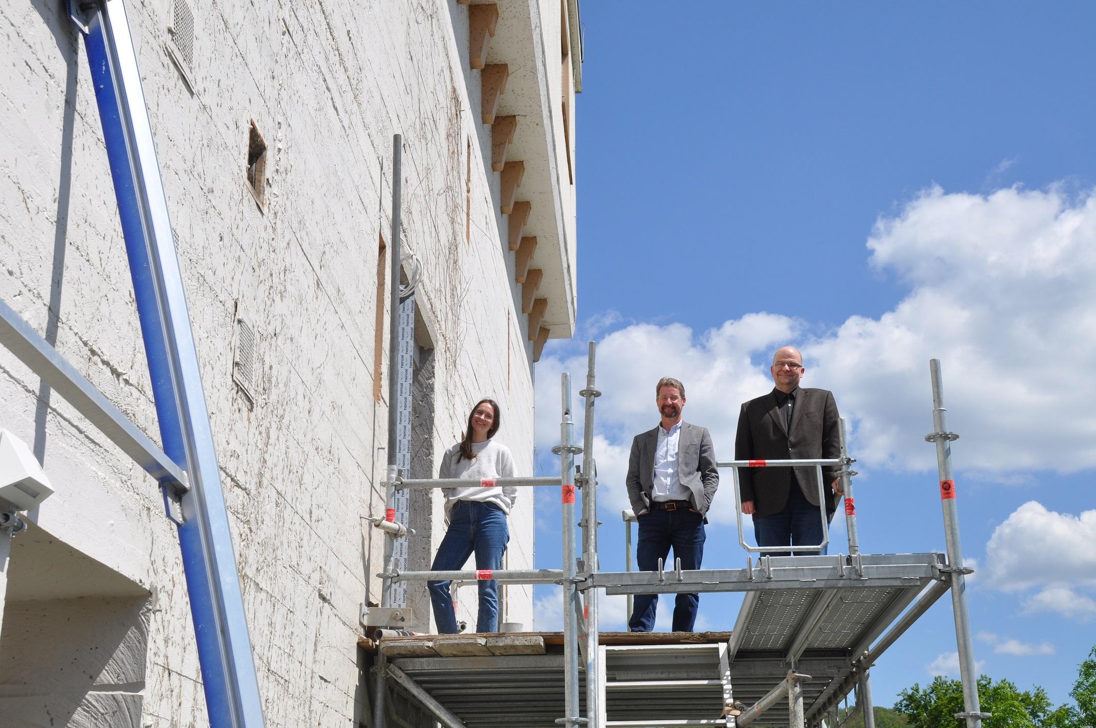 Drei Menschen stehen auf einem Gerüst neben einem massiven Gebäude