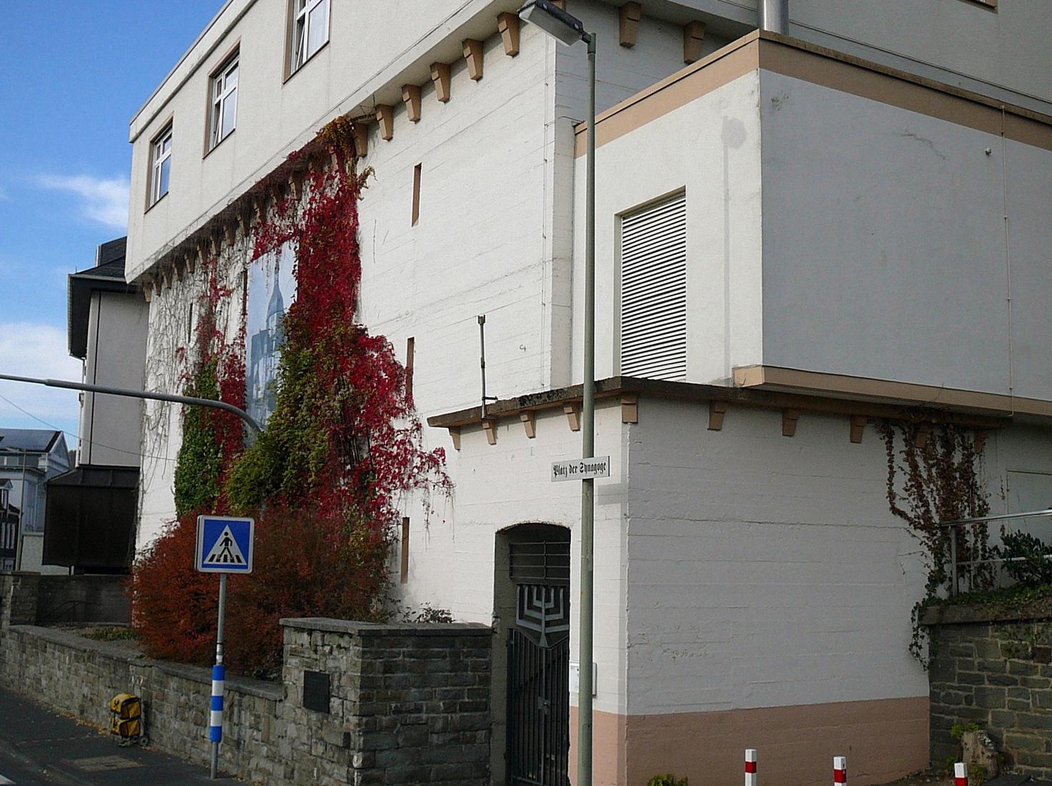 Großes, eckiges massives Gebäude. Eine Seitenwand ist zum Teil mit Efeu bewachsen. Zwischen dem Efeu ist das Bild der Siegener Synagoge an der Gebäudewand angebracht.