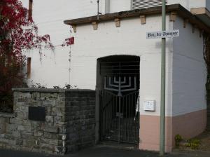 """Geschlossenes, geschmiedetes Eingangstor, dessen oberer Teil wie eine jüdische Menora geformt ist. Neben dem Eingang ein Straßenschild mit dem Aufdruck """"Platz der Synagoge""""."""