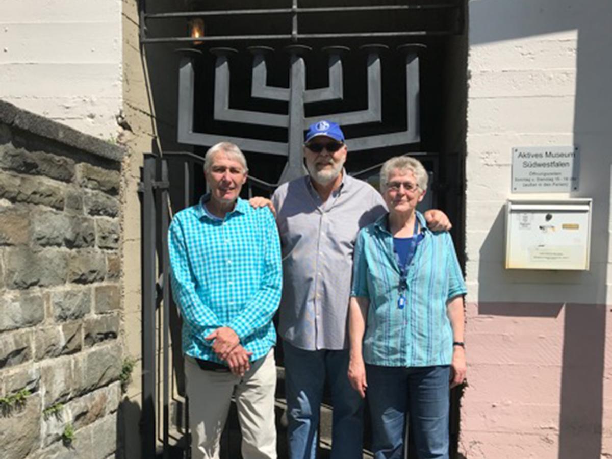 Zwei Männer und eine Frau stehen vor einem geschmiedeten Eingangstor zu einem Gebäude.