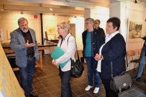 Fünf Menschen stehen vor einer Ausstellungstafel. Ein Mann links im Bild redet animiert, die restlichen Personen hören ihm zu.