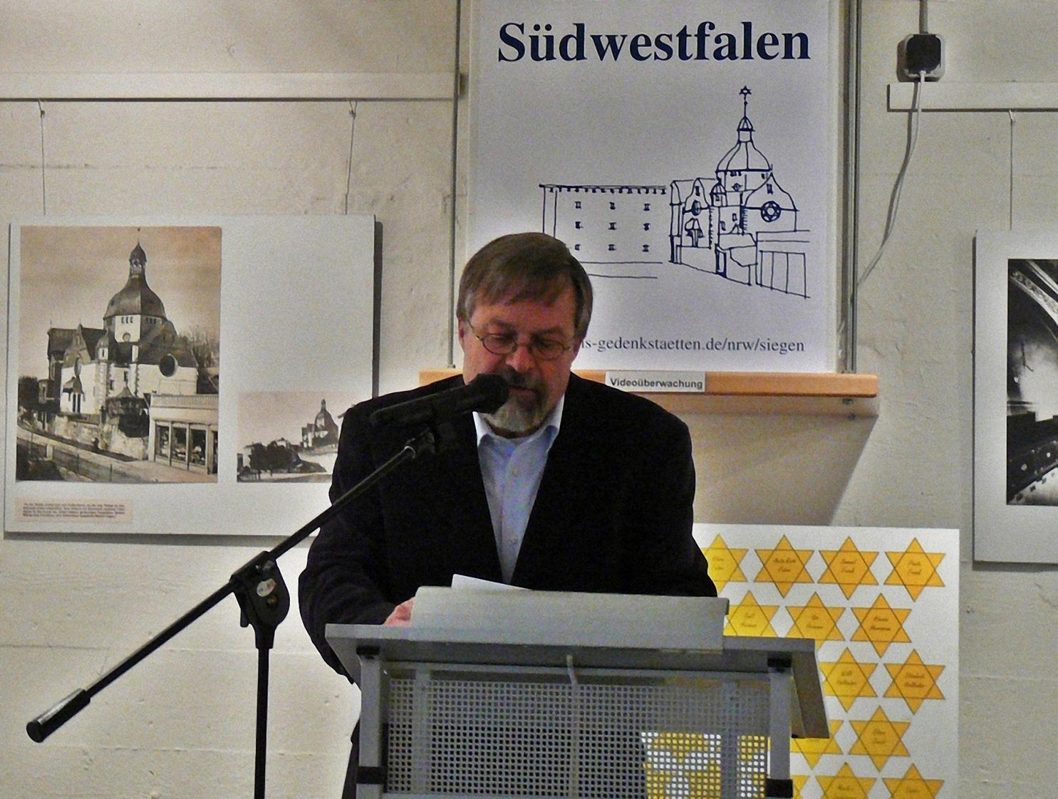 Ein Mann spricht an einem Pult in ein Mikrofon. Im Hintergrund Ausstellungstafeln.