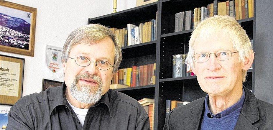Zwei ältere Männer mit Brille blicken in die Kamera. Im Hintergrund ein Bücherregal.